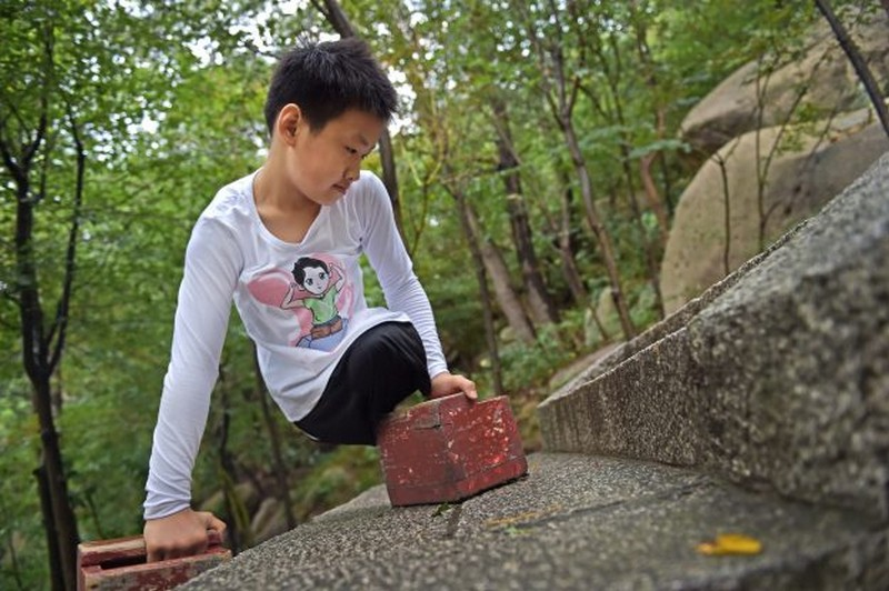 Wanderlust Tips Magazine   11-year-old legless boy conquered 900m high moutain in China